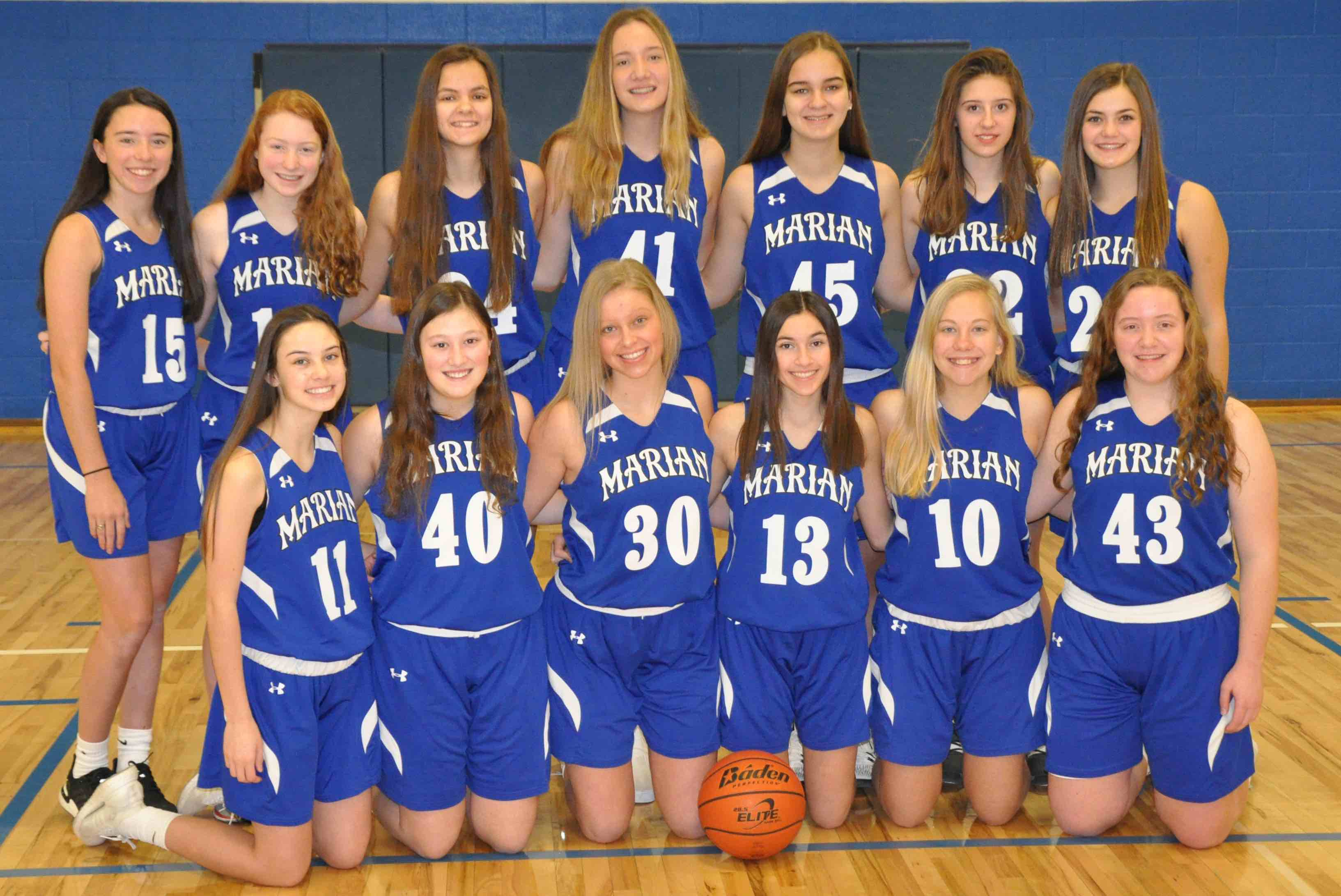 Reserve basketball team in blue jerseys posing for picture in gym
