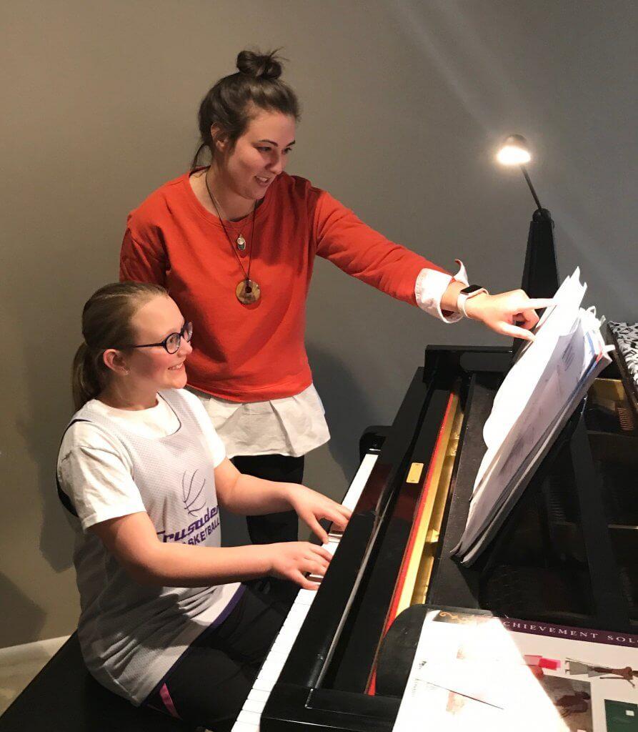 Jen Cimino instructing a child at a piano.