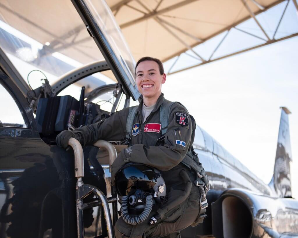 Marian alumnae Simone Duryea standing in front of a fighter jet in her Air Force uniform.